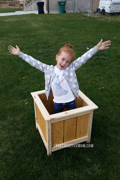 wood box planter outside with girl inside box